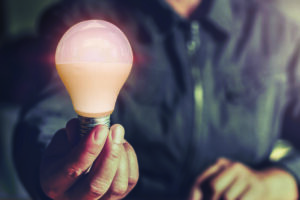 man holding an LED lightbulb out in front of him